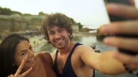 Молодые люди в влюбленности делая изображения на пляже акции видеоматериалы