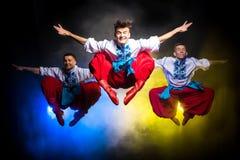 3 молодые люди в украинских национальных костюмах танцует и скачет на темную предпосылку с дымом Стоковое Фото