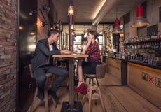 3 молодые люди говоря, сидя кофейня внутри помещения Стоковая Фотография
