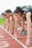 Молодые люди готовое для того чтобы участвовать в гонке на поле следа Стоковое Фото