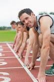 Молодые люди готовое для того чтобы участвовать в гонке на поле следа Стоковая Фотография