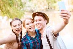 3 молодые люди делая selfie в парке Стоковая Фотография