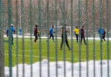 Молодые люди играет футбол в снеге в зиме Взгляд через загородку Отдых, активные внешние игры, спорт селективно Стоковая Фотография