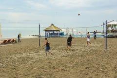Молодые люди играя волейбол пляжа на песке морем Стоковые Изображения RF