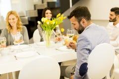 Молодые люди имеет обедающий и провозглашать с вином Стоковые Изображения RF