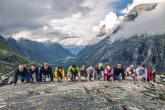 Молодые люди имеет потеху на верхней части горы, Trollstigen, стоковое изображение