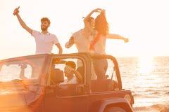 5 молодые люди имея потеху в обратимом автомобиле на пляже на заходе солнца Стоковое Фото
