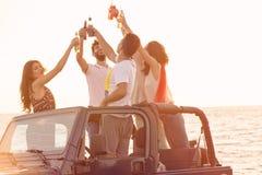 5 молодые люди имея потеху в обратимом автомобиле на пляже на заходе солнца Стоковая Фотография