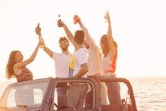 5 молодые люди имея потеху в обратимом автомобиле на пляже на заходе солнца Стоковое фото RF