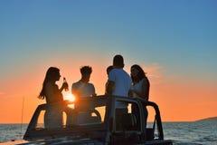 5 молодые люди имея потеху в обратимом автомобиле на пляже на заходе солнца Стоковое Изображение RF