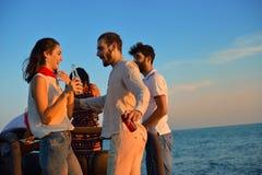 5 молодые люди имея потеху в обратимом автомобиле на пляже на заходе солнца Стоковые Фото