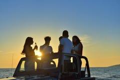 5 молодые люди имея потеху в обратимом автомобиле на пляже на заходе солнца Стоковая Фотография RF