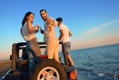 5 молодые люди имея потеху в обратимом автомобиле на пляже на заходе солнца Стоковое Изображение