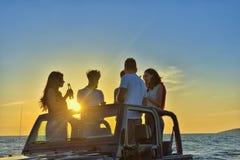 5 молодые люди имея потеху в обратимом автомобиле на пляже на заходе солнца Стоковые Изображения RF