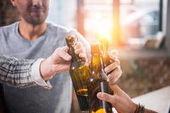 Молодые люди имея потеху и clinking пивные бутылки Стоковое Фото