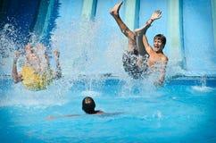 Молодые люди имея потеху на водных горках в парке aqua Стоковая Фотография
