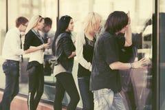 Молодые люди и женщины моды смотря через окно мола Стоковые Фотографии RF