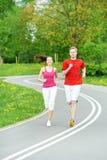 Молодой человек и женщина jogging outdoors Стоковые Фотографии RF