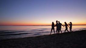 Молодые люди идя на пляж вечера сток-видео
