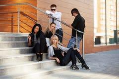 Молодые люди моды сидя на шагах Стоковая Фотография
