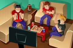 Молодые люди наблюдая американский футбол Стоковая Фотография RF