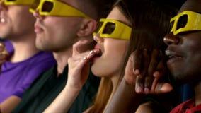 Молодые люди наблюдая кино на театре кино видеоматериал