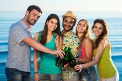 Молодые люди напитков питья на пляже Стоковая Фотография