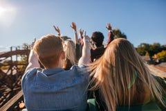 Молодые люди на захватывающей езде русских горок стоковое изображение