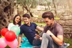 3 молодые люди на пикнике сидя на одеяле под оливкой Стоковая Фотография RF