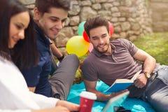 3 молодые люди на пикнике сидя на одеяле под оливкой Стоковая Фотография