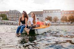 Молодые люди на шлюпке педали в озере Стоковая Фотография RF