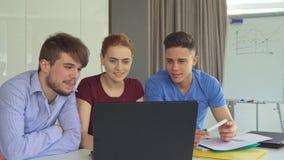 Молодые люди обсуждает что-то на компьтер-книжке на офисе сток-видео