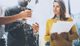 Молодые люди обсуждая ideasin дела офис Укомплектуйте личным составом держать бумагу его руки и разговаривать с женщиной горизонт Стоковая Фотография