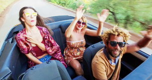 Молодые люди партии танцуя к музыке в рассортированном автомобиле с откидным верхом, акции видеоматериалы