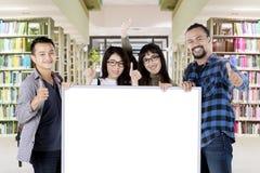 Молодые люди показывая одобренный знак и доска Стоковое Фото