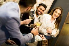 Молодые люди празднуя и провозглашать с белым вином Стоковое фото RF