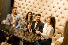 Молодые люди празднуя и провозглашать с белым вином Стоковое Изображение RF