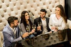 Молодые люди празднуя и провозглашать с белым вином Стоковое Фото