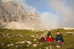 Молодые люди располагаясь лагерем пока пеший туризм в горах Стоковое Фото