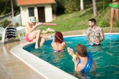 Молодые люди распыляя один другого в бассейне Стоковое Изображение RF