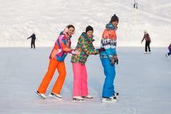 Молодые люди, друзья, катание на коньках зимы на замороженном озере Стоковое фото RF