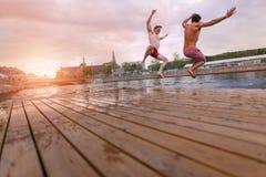 Молодые люди скача в озеро в городе Стоковые Изображения RF