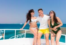 Молодые люди смеясь над и стоя на яхте на солнечном summe Стоковое Изображение