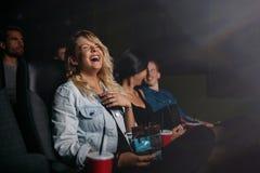 Молодые люди смотря кино и смеяться над Стоковые Изображения RF