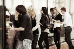 Молодые люди смотря через окна магазина Стоковое Изображение