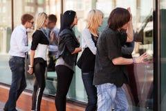 Молодые люди смотря через окно мола Стоковые Изображения RF