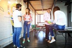 Молодые люди собирает в современный офис имеет встречу и метод мозгового штурма команды пока работающ на компьтер-книжке и выпива стоковые фотографии rf