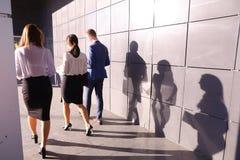 3 молодые люди, студенты, 2 девушки и парень, идет назад к пришло Стоковая Фотография