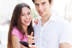 Молодые люди с мобильным телефоном Стоковые Изображения