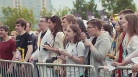 Молодые люди толпится движения имея потеху на внешнем музыкальном фестивале лета сток-видео